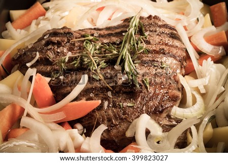 Large piece of fresh beef meat prepared on a grill pan with herbs and vegetables. Toned.