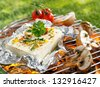 Large portion of seasoned halloumi or feta cheese grilling in tin foil over hot coals in a barbecue outdoors on green grass - stock photo