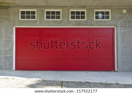 Large red garage door and four windows.