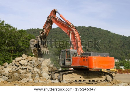 Large track hoe excavator digging out old rock during preparation at a new commercial development road construction project