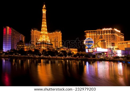 Las Vegas, Nevada, USA - Sept. 25, 2014: Nightlife along the famous Las Vegas Strip with Paris and Planet Hollywood Casinos reflecting in the Bellagio lake in Las Vegas, Nevada, USA - Sept. 25, 2014