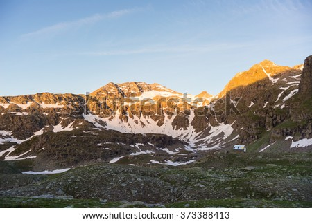 Last warm sunlight over rocky mountain peaks of the Alps. Extreme terrain landscape at high altitude in National Park, Italy.