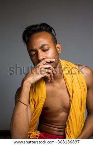 Latin man posing indoor over a grey wall