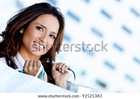 Latin shopping woman holding paperbags and smiling