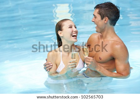 Laughing attractive happy couple with champagne wine in swimming pool