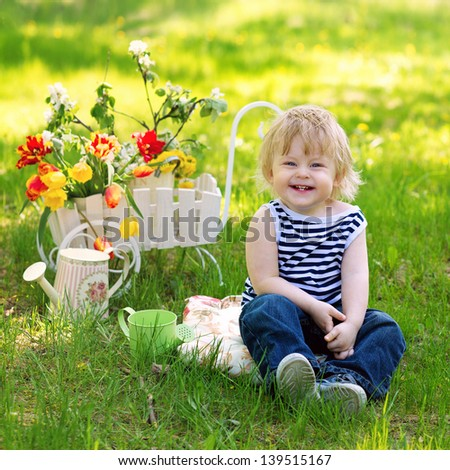 Laughing baby boy sitting on the fresh green grass in the garden near decorative wooden wheelbarrow full of flowers