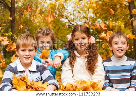 Laughing children and yellow leaves falling on them