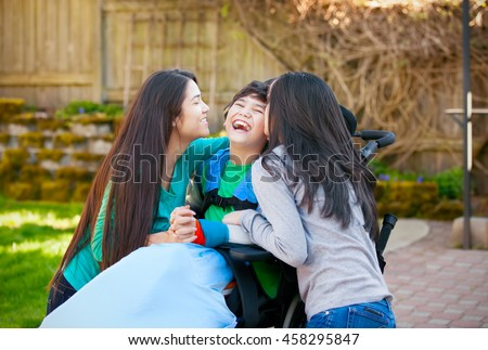 Laughing disabled boy in wheelchair being hugged and kissed by two teenage girls on patio outdoors