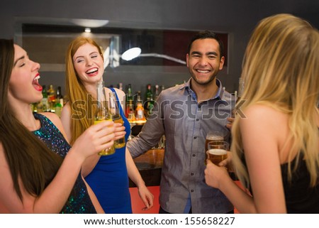 Laughing friends drinking beers and chatting in the nightclub