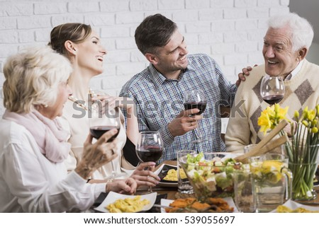 Laughing members of the family holding glasses of wine during dinner