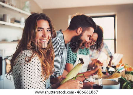 Laughing woman talking and preparing meals at table full of vegetables and pasta ready for cooking in kitchen