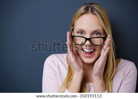 laughing woman wearing eyeglasses against a dark grey background