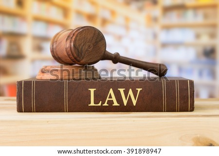 Law book with a judges gavel on desk in the library. Concept of jurisprudence, legal education.