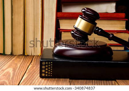 Law concept - Law book with a wooden judges gavel on table in a courtroom or law enforcement office.