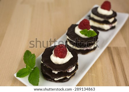 Layers of chocolate biscuits filled with whipped cream and small raspberry pieces and decorated with a sprig of mint and a raspberry on top.