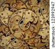 Layers of rusty brass mechanical watch mechanism. - stock photo