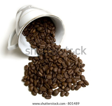 Laying coffee cup with spilled coffee beans