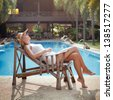 lazy day, idleness, woman sleeping in the deck chair near the swimming pool - stock photo