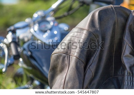 leather jacket in the focus of a motorcycle chopper, bokeh of chrome