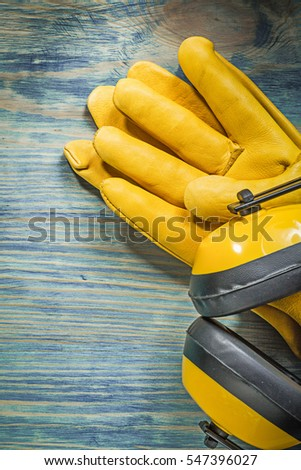 Leather safety gloves noise insulation ear muffs on wooden board construction concept.