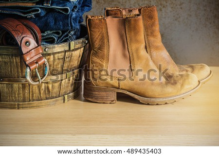 Leather shoes and clothes in basket on the wooden.