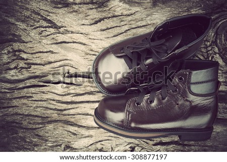 leather shoes on wooden table with vintage tone
