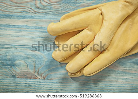 Leather yellow safety gloves on wood board construction concept.