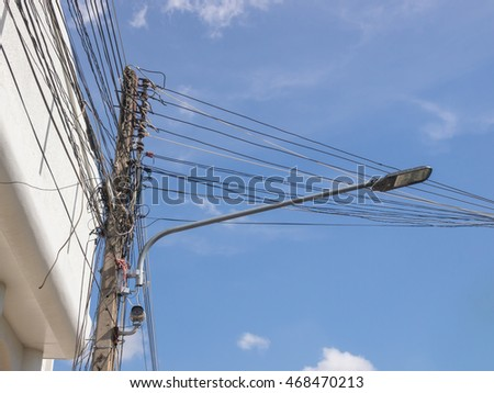 LED street light with messy wires against sky background.