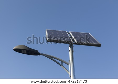 LED street light with solar panels, over blue sky