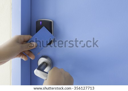 left hand hold key card touch on black electronic pad lock access control with right hand turn stainless steel door handle on blue door