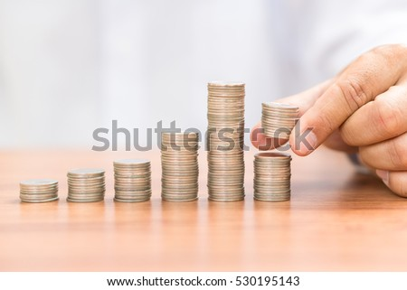 Left hand putting add coin to coin stack, saving money concept.