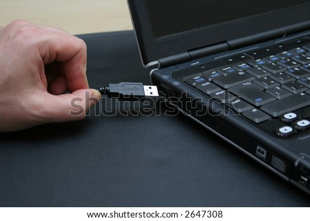 Left-handed businessman connecting his portable