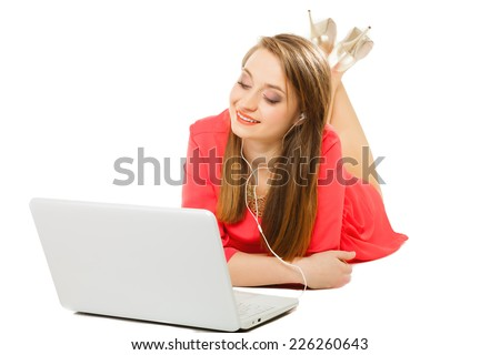 Leisure free time, music, online and internet concept - happy teenage girl with earphones and laptop computer