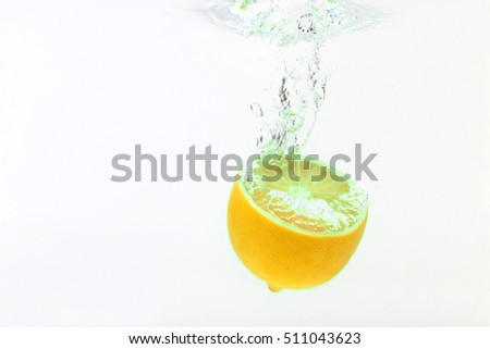 lemon falling in water on white background