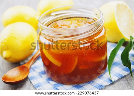Lemon jam in the glass jar on the wooden table