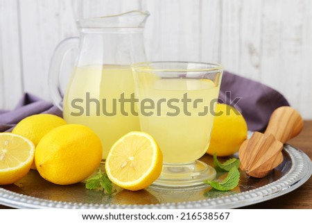 Lemon juice with fresh lemon and mint in glass jug on wooden background