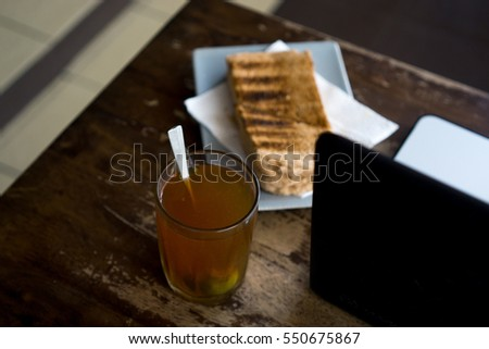 Lemon Tea and laptop for business, relax concept. Selective focus on drink, bread or laptop