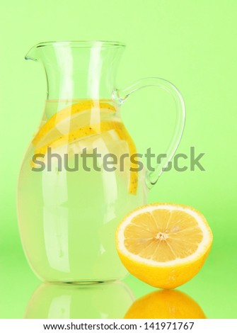 Lemonade in pitcher on green background