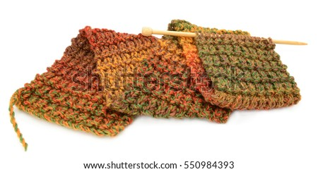 Length of knitting for a scarf in autumnal colours on a knitting needle, isolated on a white background