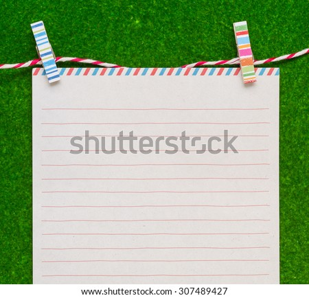Letter paper with colorful clips on green background
