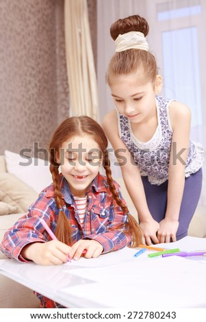 Letter to Santa. Two beautiful smiling girls sitting at table and writing