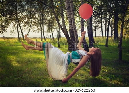 Levitating woman with red balloon and long dress.Vintage effect.