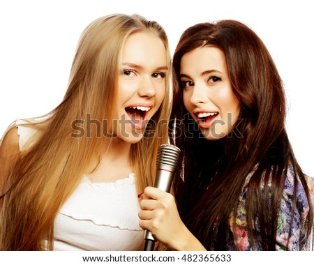 life style, happiness, emotional and people concept: two beauty hipster girls with a microphone singing and having fun