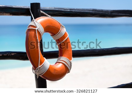 Lifebuoy ring on wooden railing near tropical beach