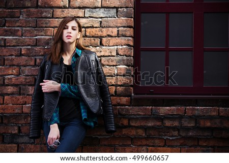 Lifestyle fashion portrait of brunette girl in rock black style, standing outdoors in the city street