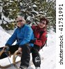 Lifestyle shot of active senior couple on sledge having fun in white winter country - stock photo