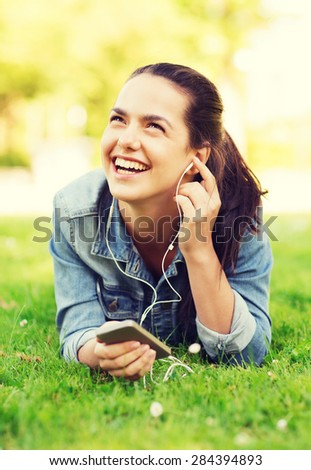 lifestyle, summer vacation, technology, leisure and people concept - laughingyoung girl with smartphone and earphones lying on grass