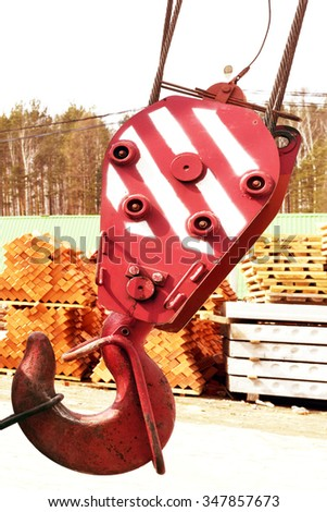 Lifting hook of a construction crane on the background of building materials