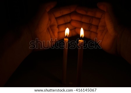 light candle burning brightly in the hand background