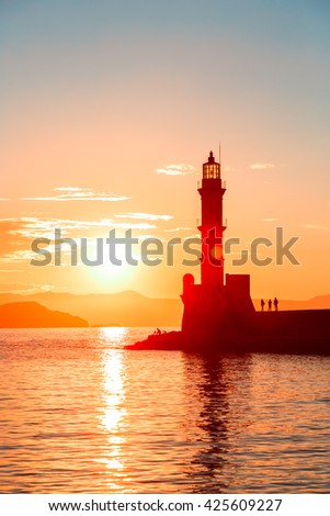 Lighthouse in old venetian harbor, port of Chania at sunset, Crete, Greece
